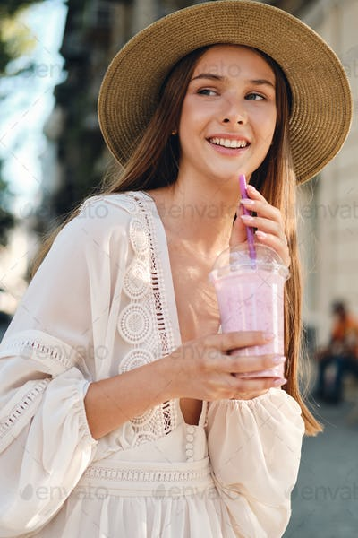 Young attractive smiling girl in white dress and hat holding smoothie joyfully on cozy city street