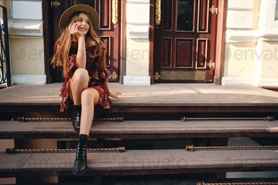 Young gorgeous woman in dress and straw hat sitting on stairs  happily looking aside on city street