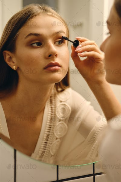 Young girl in white dress and earrings standing near mirror dreamily applying mascara in bathroom