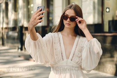 Attractive girl in sunglasses and stylish dress thoughtfully taking selfie on cozy city street