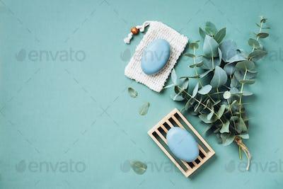 Wooden soap dish, soap, eucalyptus over green background. Zero waste, natural organic bathroom tools