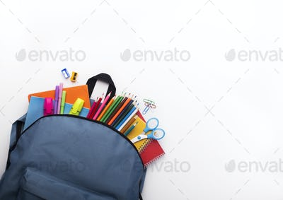 School backpack with colored stationery on white background