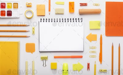 Orange colored office stationery and notepad on white
