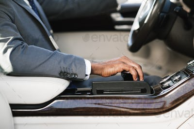 Businessman driving car, holding hand on gearbox