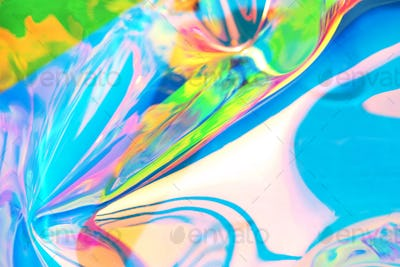 Holographic iridescent surface. Copy space. Bright colorful hologram background. Wrinkled abstract