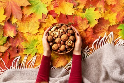Autumn flat lay. Woman hands holding wooden bowl with mixed nuts. Healthy food and snack. Vegan