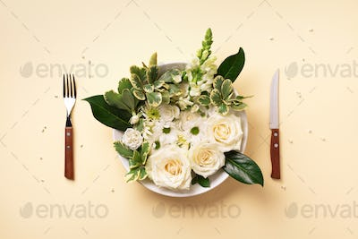 White flowers on plate, fork, knife over pastel yellow background. Healthy eating, vegan diet