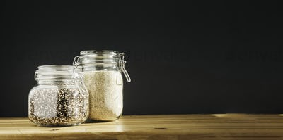 White and brown raw organic quinoa in glass storage containers. Healthy cooking, clean eating, zero