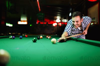 Young attractive man playing pool in bar