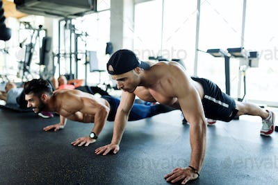 Two strong men doing push-ups in gym
