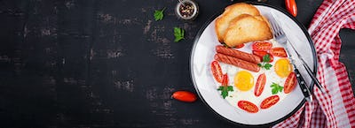 English breakfast - fried egg,  tomatoes, sausage,  and toasts.