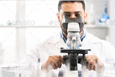 Adjusting microscope in laboratory