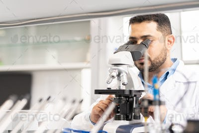 Arabian scientist using microscope
