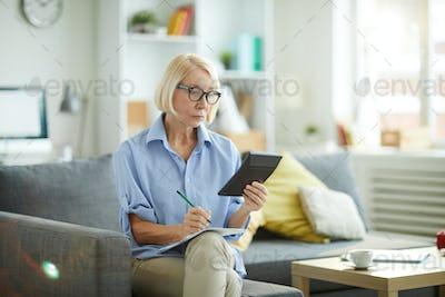 Woman Calculating Budget at Home