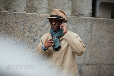 Modern African Man Speaking by Phone in City