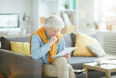 Frowning Senior Man Looking at Document