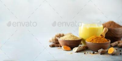 Healthy vegan turmeric latte or golden milk, turmeric root, ginger powder, black pepper over grey