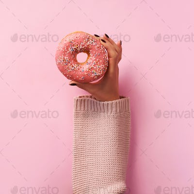 Female hands holding donut over pink background. Top view, flat lay. Sweet, dessert, diet concept