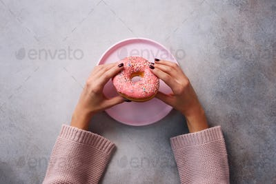 Female hands holding donut on pink plate over stone background. Top view, flat lay. Sweet, dessert