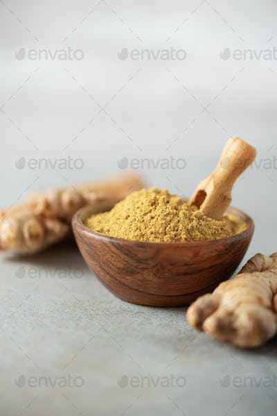 Ginger root and ginger powder in wooden bowl over grey concrete background with copy space. Immune