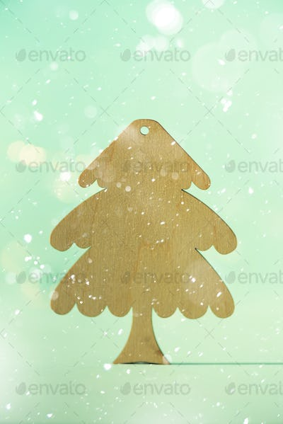 Greeting card in minimal style. Wooden Christmas tree on blue background with copy space, lights