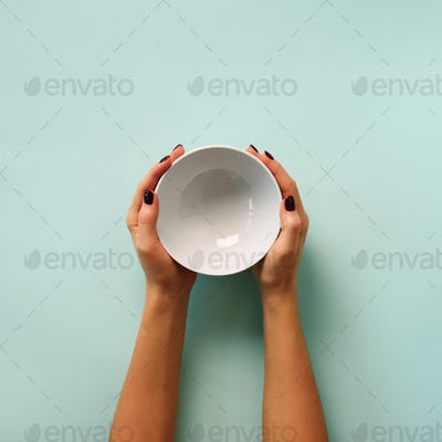 Female hand holding white empty bowl on blue background with copy space. Healthy eating, dieting