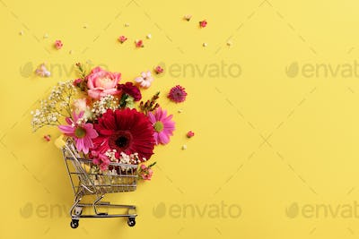Shopping trolley with flowers on yellow punchy pastel background. Banner with copy space. Top view