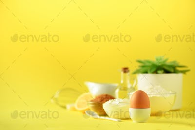 Healthy baking ingredients - butter, sugar, flour, eggs, oil, spoon, brush, whisk, milk over yellow