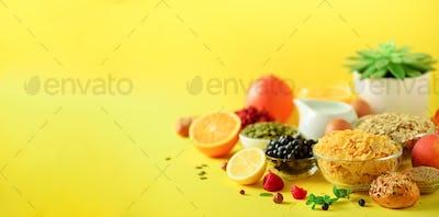 Vegetarian breakfast. Soft boiled egg, oat flakes, nuts, fruits, berries, milk, yogurt, orange