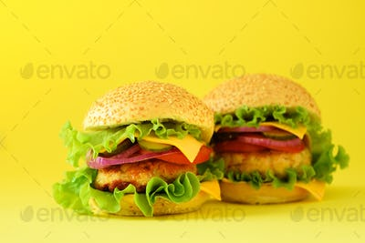 Fast food - juicy hamburger, french fries potatoes and cola drink on yellow background. Take away