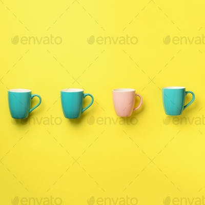 Pattern from blue and pink cups over yellow background. Square crop. Birthday party celebration