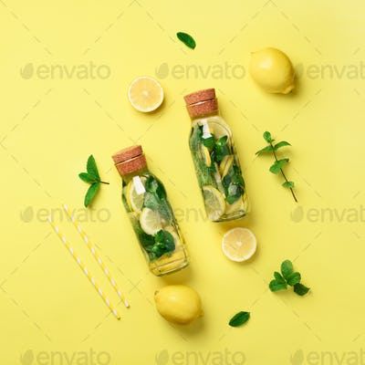 Bottle of detox water with mint, lemon on yellow background. Flat lay. Square crop. Citrus lemonade