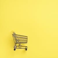 Shopping cart on yellow background. Minimalism style. Creative design. Top view with copy space