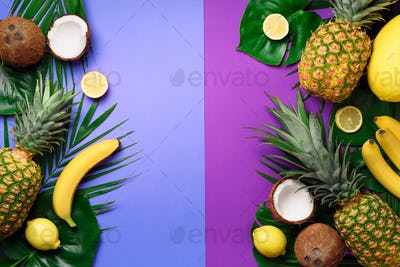 Exotic pineapples, coconuts, banana, melon, lemon, tropical palm and green monstera leaves on purple