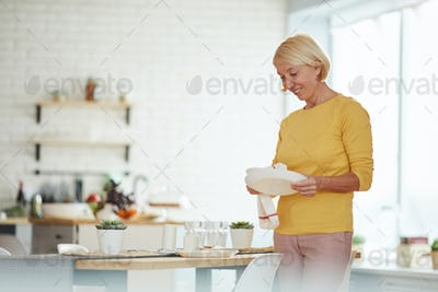Mature woman wiping plate with dish towel