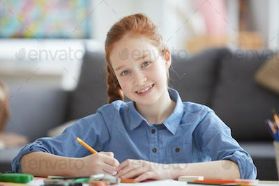 Smiling Red Haired Girl Drawing Pictures