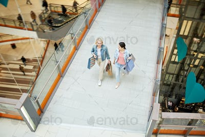 Excited mother and daughter talking while walking over mall