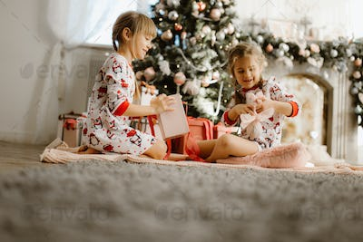 Two happy little sisters in pajamas sit on the carpet and open New Year's gifts in the light