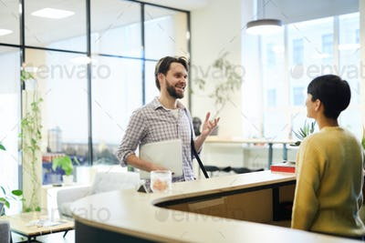 Cheerful man asking receptionist to check in