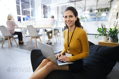 Beautiful woman with badge working in cozy office