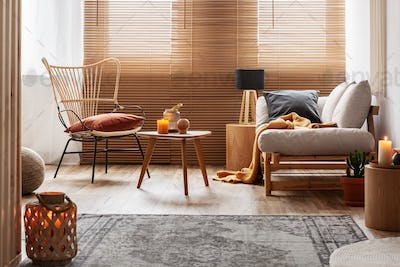 Stylish natural living room with raw wooden furniture and orange accents