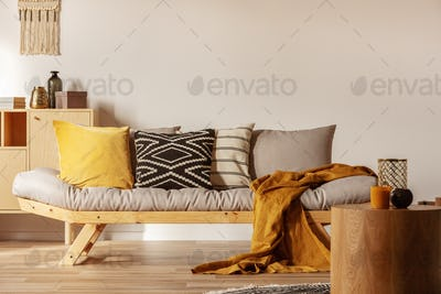 Copy space on empty white wall of fashionable living room interior with yellow and orange accents