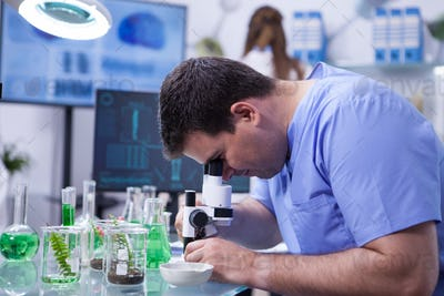 Caucasian scientist man in a biotechnology lab Looking through microscope