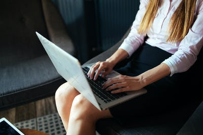Close-up picture of attractive woman typing on laptop