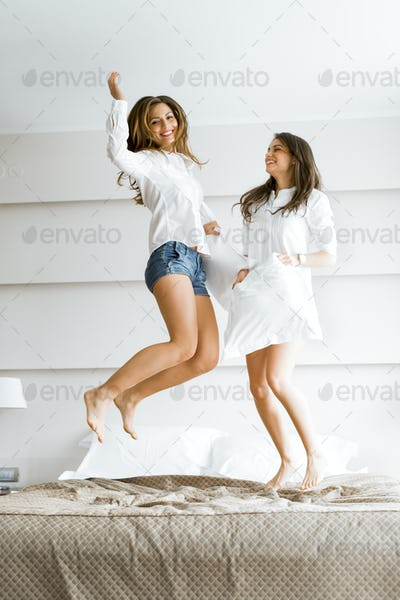Two beautiful women jumping from joy on bed and fighting with pi