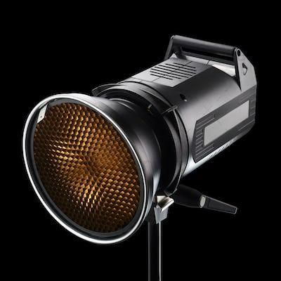 Photography studio flash with honeycomb on black background