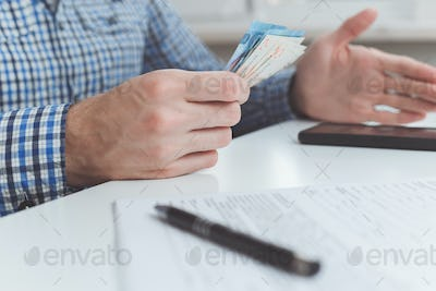 Tough financial conditions. Businessman holds money and gestures specifically