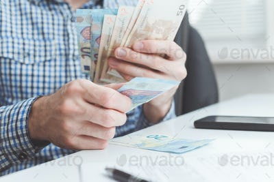 Businessman counts a money in office