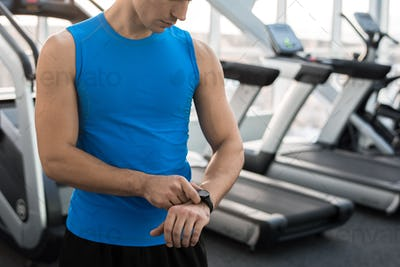 Man Checking Fitness Tracker in Gym