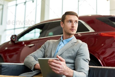 Handsome Client Waiting in Car Showroom